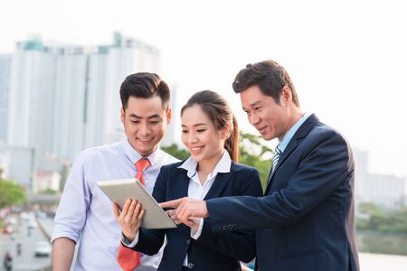 Asian businessman in suit showing online presentation on digital tablet to his colleagues while they standing