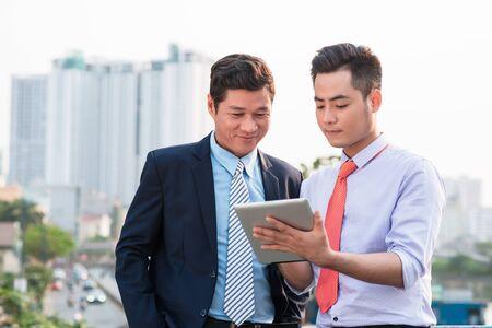 Jeunes beaux hommes d'affaires discutant du projet sur une tablette numérique à l'extérieur