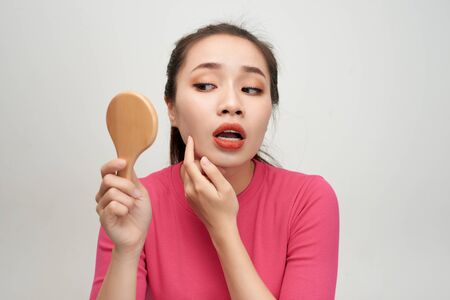 Woman holding a mirror, touch and worrying about her face 免版税图像