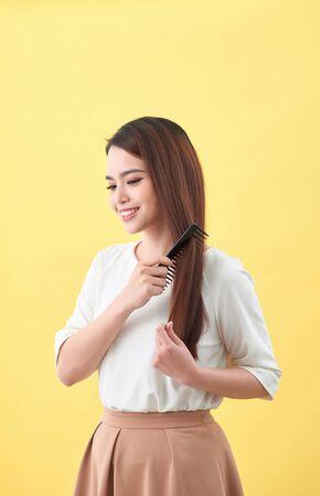 Happy woman brushing her beautiful healthy wavy hair