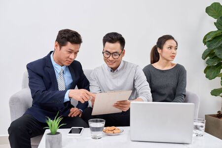 Real estate agent working with couple of customers in the office Stock Photo