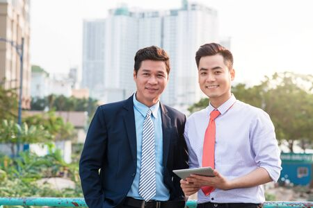 Young handsome businessmen discussing project on digital tablet computer outdoors
