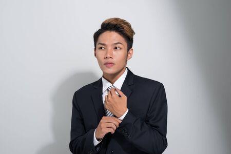 Asian businessman Fixing Cufflinks his black Suit Stock Photo