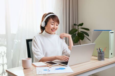 Beautiful Asian woman calling video by laptop at working place home.