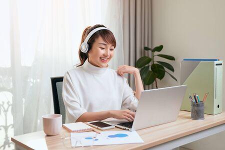 Schöne asiatische Frau, die Video per Laptop am Arbeitsplatz nach Hause anruft.