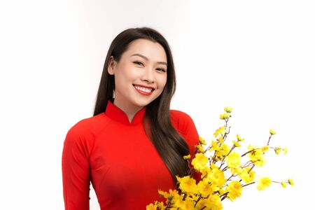 Beauty woman in Vietnamese traditional dress ao dai, apricot blossom in Lunar New year.