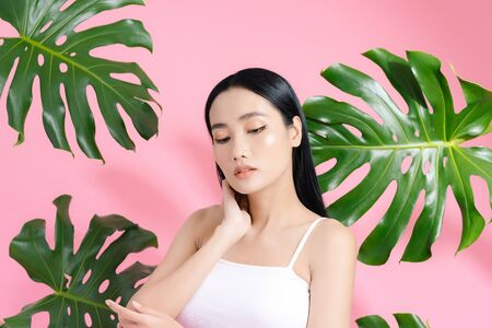Portrait of young and beautiful Asian woman touching her face with perfect smooth skin in tropical leaves. Concept of natural cosmetics and skincare.
