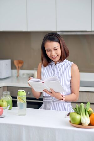 Pretty woman reading recipe to make detox drink in kitchen.