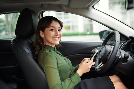 Jonge mooie vrouw die smartphone gebruikt tijdens het autorijden Stockfoto