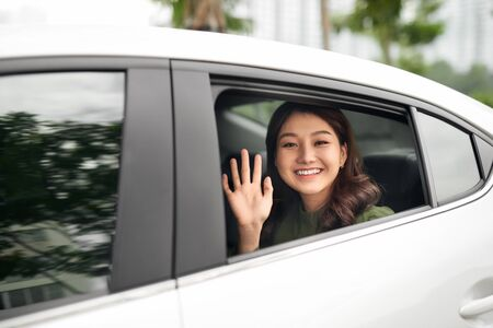 Woman in car. Beautiful young woman looking out from a car and looking at camera