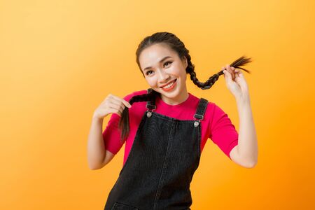 Cute mischievous young asian woman pulling her pigtails