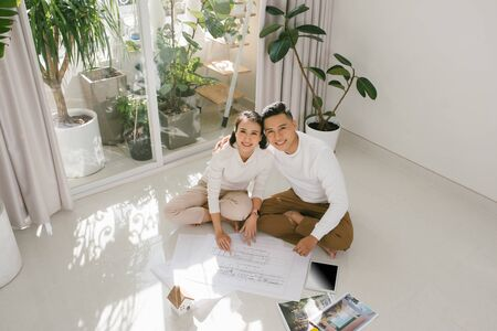 Young couple looking blueprints of they new house. Planning interior design