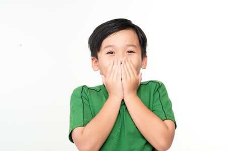 Cute asian boy covers his mouth with his hands.