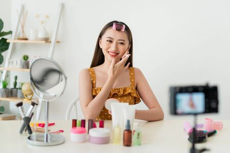 Best powder. Pleasant young woman showing her cosmetics on camera while recommending it to her viewers