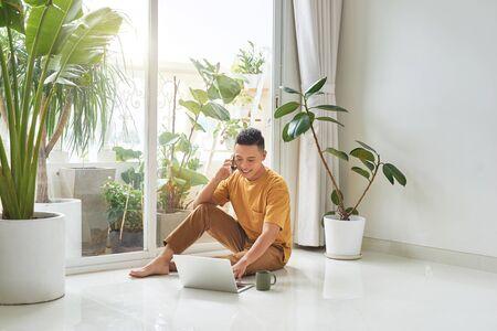 Mann, der auf dem Handy mit Laptop spricht, der zu Hause auf dem Boden sitzt Standard-Bild
