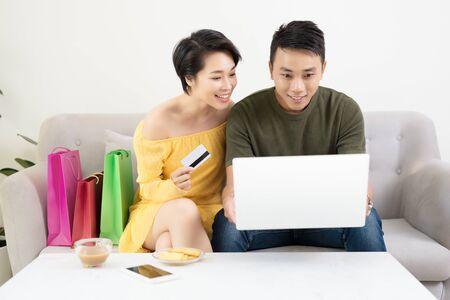 Joven pareja asiática haciendo compras en línea en un portátil en casa Foto de archivo