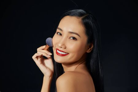 Beauty portrait of smiling half-naked woman with fresh skin applying makeup with soft brush isolated over black background