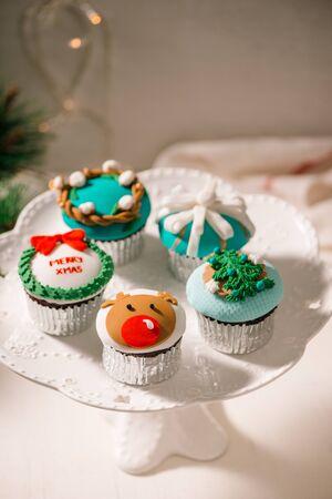 Seasonal festive christmas mini dessert cupcakes in traditional red green decorative symbols elements