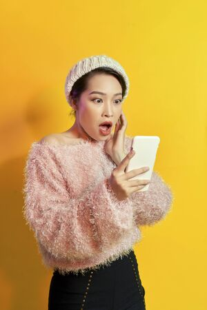 Fille choquée regardant l'écran du téléphone avec la bouche ouverte. Portrait en plein air d'une jeune femme surprise vêtue d'une tenue de fourrure rose et tenant un smartphone. Banque d'images