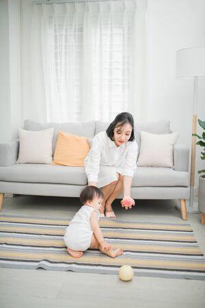 Glückliches kleines Mädchen mit Mutter, die Spielzeug in der Nähe des Sofas im Wohnzimmer spielt.