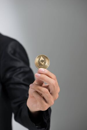man's hand holding golden Bitcoin isolated on white background