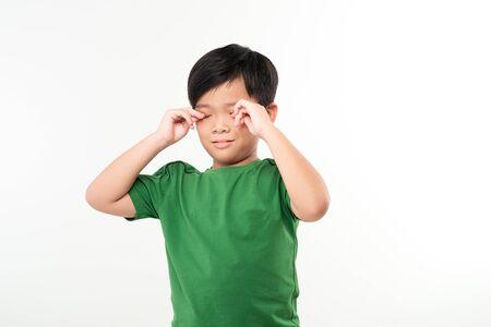 School boy rubbing eyes after long time homework