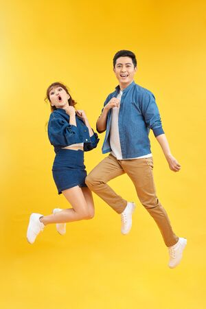 Full length body size photo funky she her he him his pair jumping high raised fists yell scream shout loud wear casual jeans denim white t-shirts isolated yellow background