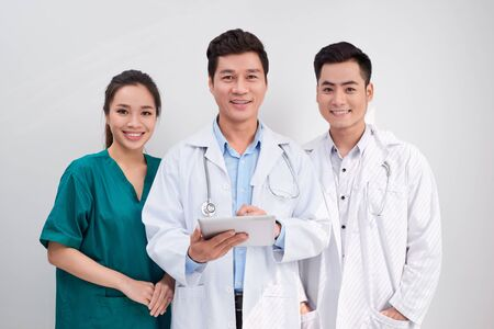 Medical team includes doctors and nurse looking at an ipad/tablet computer together