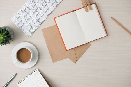 Modern minimalistic work place. Keyboard, notebook, envelope, glasses, pen, pencil, coffee on wood table. Top view with copy space, flat lay