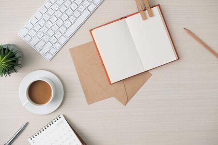 Posto di lavoro minimalista moderno. Tastiera, taccuino, busta, occhiali, penna, matita, caffè sul tavolo di legno. Vista dall'alto con spazio di copia, disposizione piatta