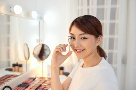 Portrait of beautiful young Asian woman looking at the mirror using eyelash curler