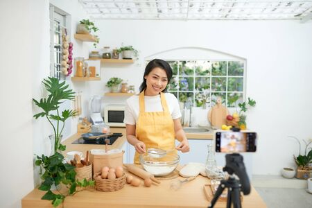 Pretty young asian female food blogger working on a new video and explaining how to cook a dish