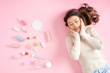 Young Asian woman sleeping on pink floor with her make up tools around. Top view