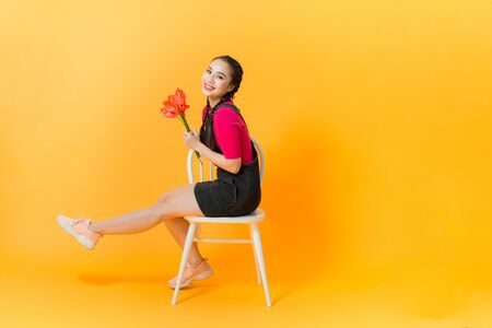 Portrait of happy beautiful Asian woman with bouquet of flowers on yellow background