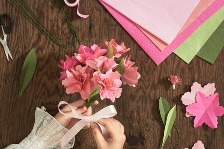 Woman making paper bouquet at wood table with color papers, scissors for valentines, holidays. Flatlay, top view. 版權商用圖片