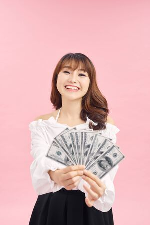 Image of delighted woman wearing basic clothes smiling and holding money cash isolated over pink background Stock Photo