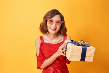 Portrait of casual young happy smiling woman hold gift box.