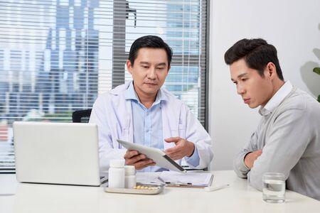 Médico asiático consulta a paciente joven