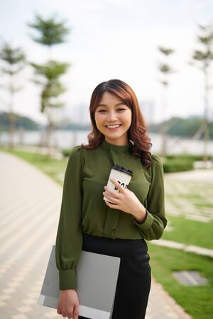 pretty young woman carrying a cup of takeaway coffee and a file in an urban park as she gives the camera a dazzling smile