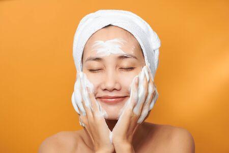 Schönes Modell, das kosmetische Cremebehandlung auf ihrem Gesicht auf orangem Hintergrund anwendet Standard-Bild