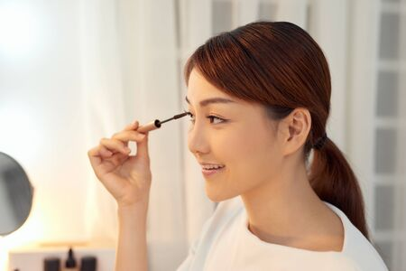 Closeup Of Beautiful Asian Woman Putting Black Mascara On Eyelashes. Beauty Cosmetics.