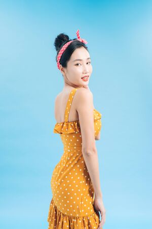 Fashionable graceful Young woman posing on blue background. Romantic adorable girl in polka dot yellow dress