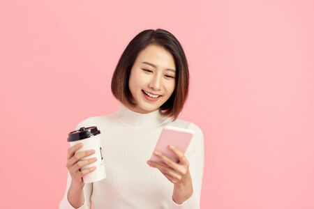 Attractive young Asian woman using mobile phone while holding coffee cup over pink background.