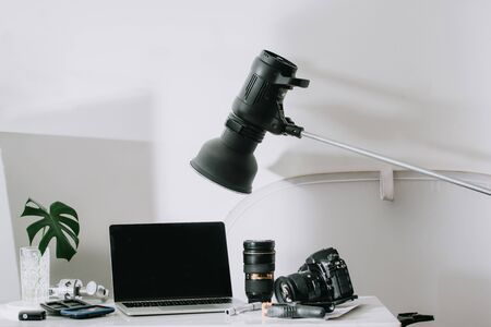 Still life working from home desk with professional photographic equipment, camera, lens, computer monitor, electronics indoors.