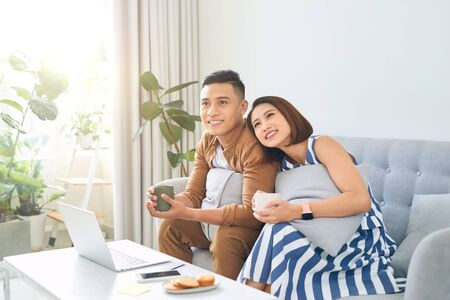 Loving Asian couple sitting on sofa and enjoying time together