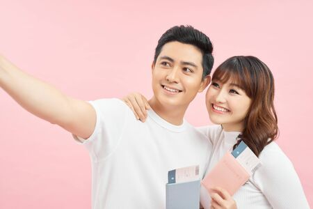 happy asian man and woman holding passports and air tickets while looking at camera isolated on pink 写真素材