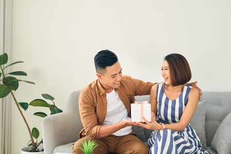 Young woman is happy and surprised with a gift from her husband/ boyfriends