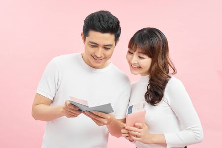 Portrait of an attractive cheerful young couple  standing isolated over pink background, showing passport with flight tickets