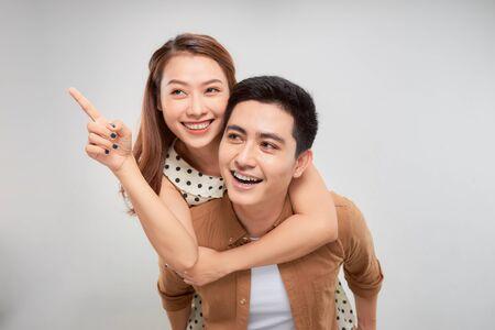 Retrato de un joven que lleva a su novia en la espalda con las manos apuntando a algo