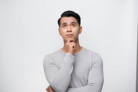 Studio shot of young Asian man thinking